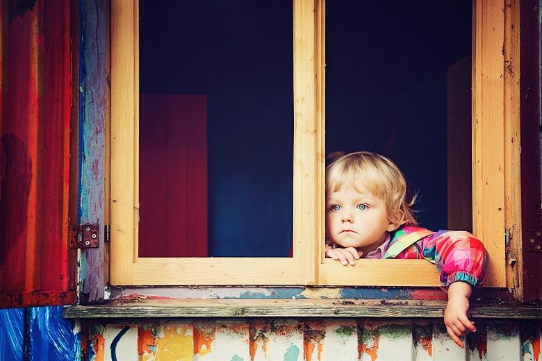 窓から外を見る子供